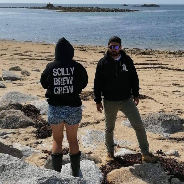 Two people wearing Scilly Brew Crew hoodies on the beach